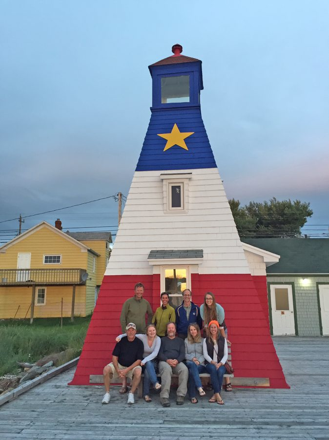Crews pose in front of a lighthouse