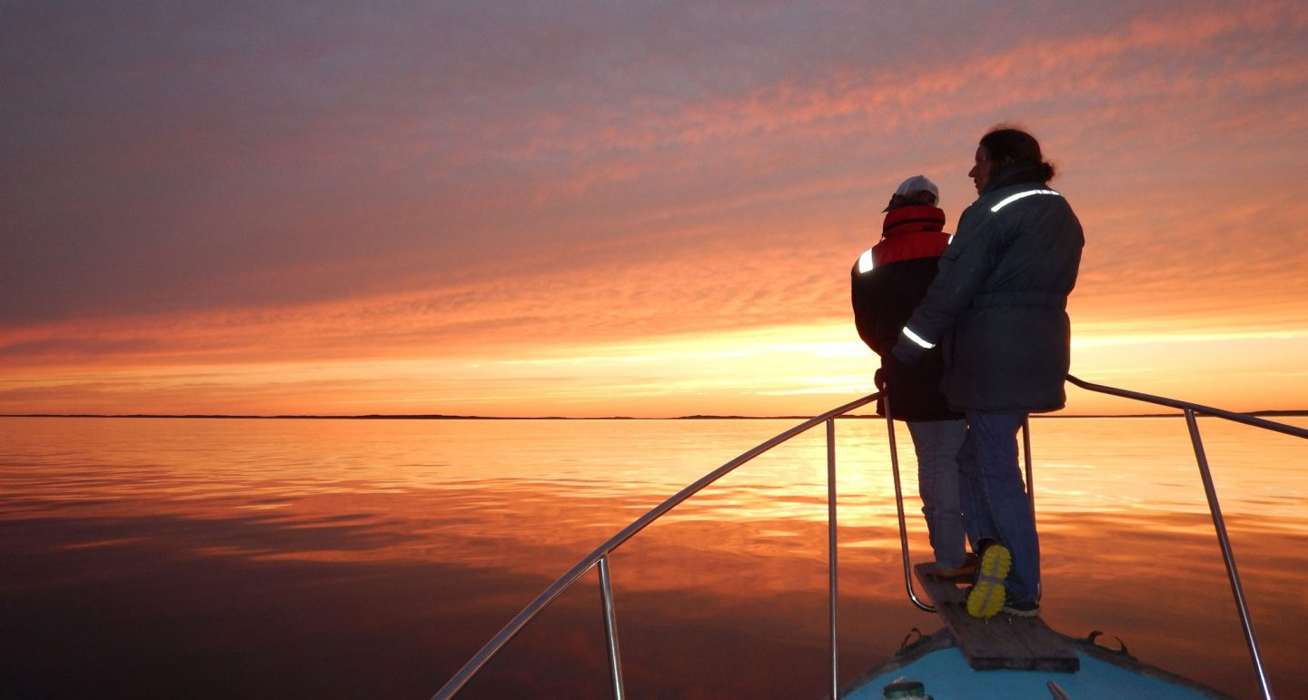 two researchers on bow sprit survey ocean at sunset