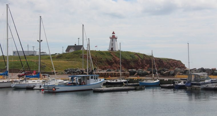 Town of Souris as seen from the water, with a view of a lighthouse and sailboats.