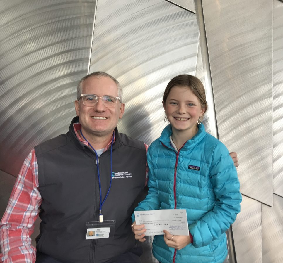 Abigail presents a check to Anderson Cabot Center Vice President Dr. John Mandelman.