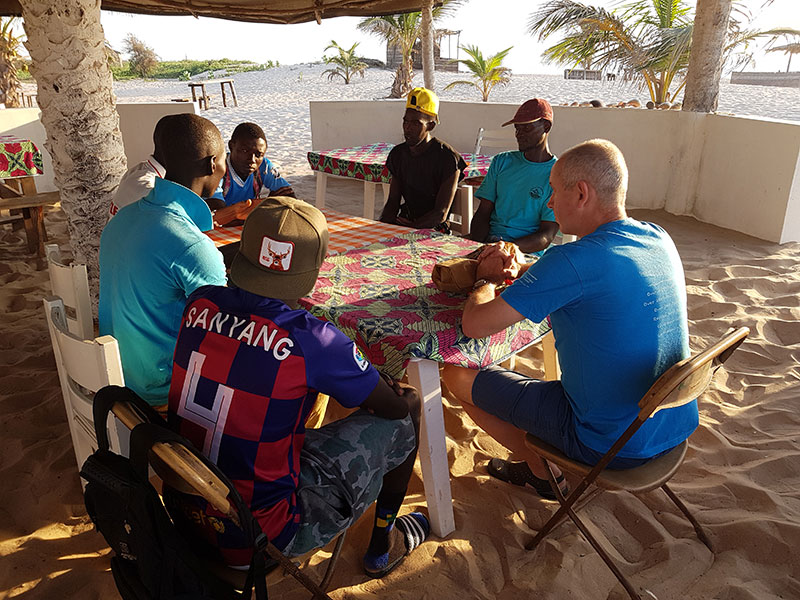 John Flynn and Omar Sanyang have a brief meeting with some local fishermen about the program