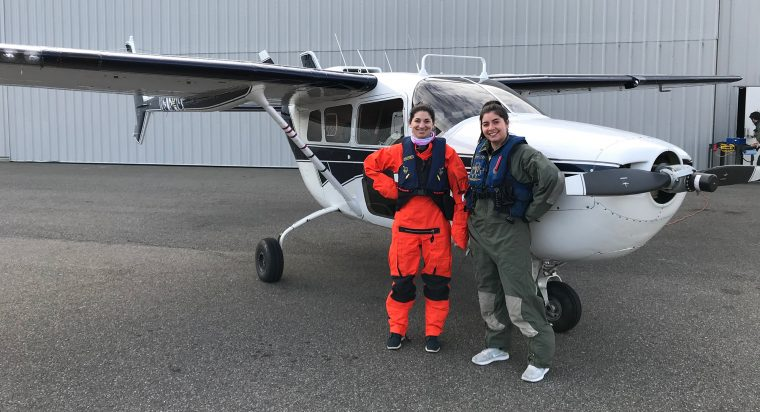 Observers Amy Warren, left, and Orla O'Brien pose in front of the Cessna Skymaster survey plane.