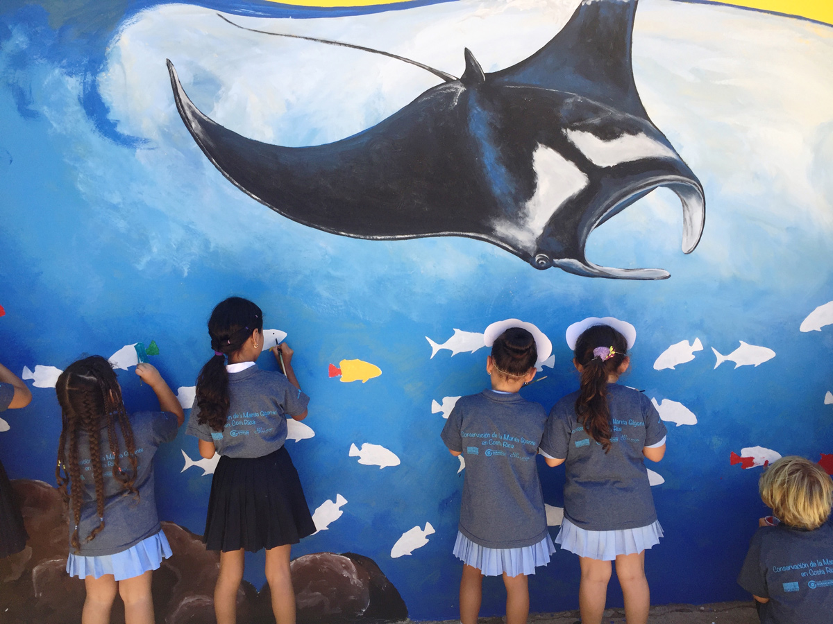 Students painting a mural on the wall of their school during an educational activity in 2018 held on Matapalo Beach, Guanacaste Costa Rica