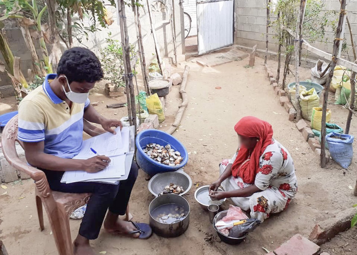 Mujas interviews a processor as she separates the shells of clams in Mutur, located on the East coast of Sri Lanka.